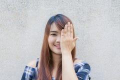 Mujer asiática hermosa joven sonriente que la cierra ojos con las manos en fondo del muro de cemento Foto de archivo