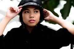 Mujer asiática hermosa que ajusta su casquillo fotografía de archivo