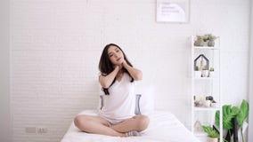 Mujer asiática hermosa que estira su cuerpo después de que ella despierte en su dormitorio en casa La hembra feliz disfruta de ma metrajes