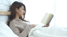 Mujer asiática hermosa que goza bebiendo el café y el libro de lectura calientes en cama en su dormitorio almacen de video