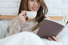 Mujer asiática hermosa que goza del café y del libro de lectura calientes en cama en su dormitorio imágenes de archivo libres de regalías