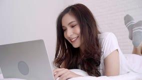 Mujer asiática hermosa que juega el ordenador o el ordenador portátil mientras que miente en la cama en su dormitorio