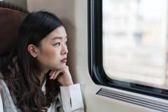 Mujer asiática hermosa que mira fuera de ventana del tren, con el espacio de la copia Imagen de archivo libre de regalías