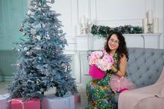 Mujer asiática hermosa que se sienta en el fondo de la Navidad diciembre imagenes de archivo