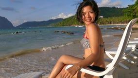 Mujer asiática hermosa que se sienta en una silla de cubierta en la playa hermosa metrajes