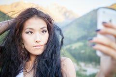 Mujer asiática hermosa que sonríe en el paisaje de la montaña Imagen de archivo