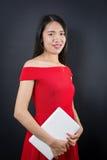 Mujer asiática hermosa que sostiene una computadora portátil Imagen de archivo