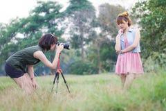 Mujer asiática hermosa que toma las fotografías de la ella es amigo Imagen de archivo libre de regalías