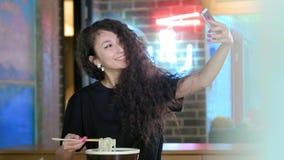 Mujer asiática hermosa que toma selfies en un smartphone La muchacha asiática joven toma la foto con la sopa del pho en la tienda almacen de video