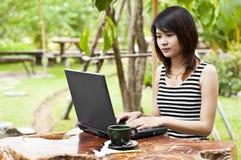 Mujer asiática hermosa que usa el cuaderno del ordenador. Imagen de archivo
