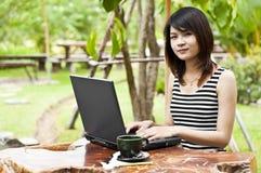Mujer asiática hermosa que usa el cuaderno del ordenador. Imágenes de archivo libres de regalías