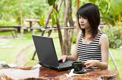 Mujer asiática hermosa que usa el cuaderno del ordenador. Fotos de archivo
