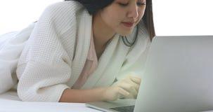 Mujer asiática hermosa que usa el cuaderno en cama almacen de metraje de vídeo