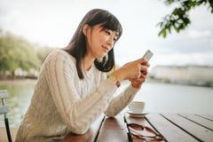Mujer asiática hermosa que usa el teléfono móvil en el café Fotos de archivo libres de regalías
