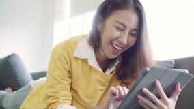Mujer asiática hermosa que usa el vídeo de observación de la tableta mientras que suéter del desgaste que miente en el sofá en sa almacen de metraje de vídeo