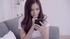 Mujer asiática hermosa que usa smartphone mientras que miente en el sofá en su sala de estar almacen de video