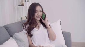 Mujer asiática hermosa que usa smartphone mientras que miente en el sofá en su sala de estar metrajes