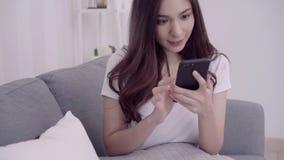 Mujer asiática hermosa que usa smartphone mientras que miente en el sofá en su sala de estar Concepto de la mujer de la forma de  almacen de metraje de vídeo