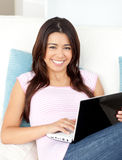 Mujer asiática hermosa que usa su computadora portátil en el sofá Fotos de archivo