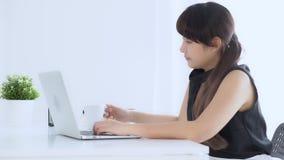 Mujer asiática independiente joven hermosa que trabaja en el café de consumición del ordenador portátil cuando es soñoliento y qu
