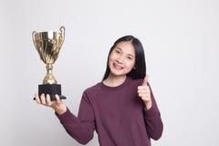 Mujer asiática joven acertada que detiene un pulgar de la demostración del trofeo foto de archivo
