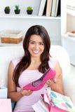 Mujer asiática joven alegre que sostiene un zapato en el sofá Foto de archivo libre de regalías