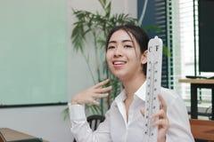 Mujer asiática joven atractiva con el termómetro que siente tan caliente en sala de estar Fotografía de archivo libre de regalías