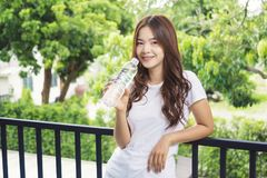 Mujer asiática joven atractiva feliz en la camiseta blanca que sostiene un bot fotografía de archivo libre de regalías
