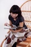 Mujer asiática joven atractiva que se sienta en el rockin Foto de archivo libre de regalías