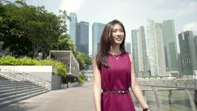 Mujer asiática joven caminando con confianza al aire libre en la cámara lenta almacen de metraje de vídeo