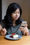 Mujer asiática joven chating el teléfono móvil con una torta Fotos de archivo libres de regalías