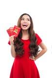 Mujer asiática joven con el gesto de rogación que le desea buena suerte Mujer joven china que muestra el dinero afortunado HOL ch Imágenes de archivo libres de regalías