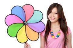 Mujer asiática joven con el molino de viento colorido Imagenes de archivo