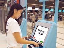 Mujer asiática joven con el pasaporte usando uno mismo - regístrese el tacto del quiosco imágenes de archivo libres de regalías
