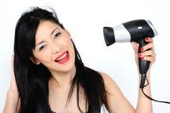 Mujer asiática joven con el pelo-secador fotos de archivo libres de regalías
