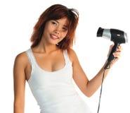 Mujer asiática joven con el pelo-secador Fotos de archivo