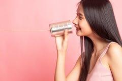 Mujer asiática joven con el teléfono de la lata fotografía de archivo