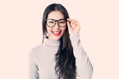 Mujer asiática joven con los vidrios que llevan de la cara sonriente aislados en w Imagen de archivo libre de regalías