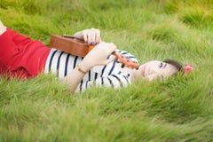 Mujer asiática joven con mentira del ukelele en jardín Imagen de archivo