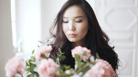 Mujer asiática joven con un manojo de flores rosadas en un florero en casa almacen de video