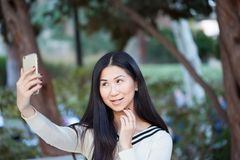 Mujer asiática joven de Charmin en un parque hermoso que sonríe y que toma Fotografía de archivo libre de regalías