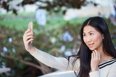 Mujer asiática joven de Charmin en un parque hermoso que toma el selfie con Foto de archivo