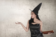 Mujer asiática joven de la bruja con el libro del encanto de la tenencia del sombrero Fotografía de archivo libre de regalías