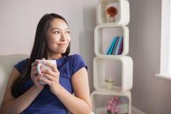 Mujer asiática joven de pensamiento que se sienta en el sofá que sostiene la taza foto de archivo libre de regalías
