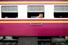 Mujer asiática joven del pelo rubio que se sienta cerca de la ventana Imagenes de archivo