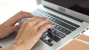 Mujer asiática joven del primer que usa el ordenador portátil para el ocio en dormitorio
