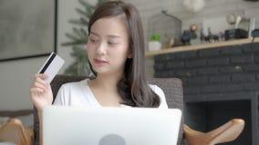 Mujer asiática joven del retrato hermoso que hace compras en línea con la tarjeta de crédito en el ordenador portátil que se sien almacen de video