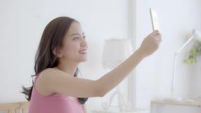 Mujer asiática joven del retrato hermoso que se sienta tomando un selfie con el teléfono móvil elegante en dormitorio por la maña almacen de video