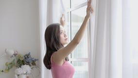 Mujer asiática joven del retrato hermoso relajar las cortinas abiertas en la ventana que mira afuera con esperanza y futuro en do metrajes