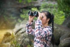 Mujer asiática joven del viajero mirando los prismáticos Imagenes de archivo